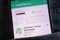 L'appli d'UTorrent sur le site Web de Google Play Store montré sur le smartphone caché dans des jeans empochent photos stock