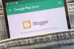 L'appli de Blogger sur le site Web de Google Play Store montré sur le smartphone caché dans des jeans empochent photo stock