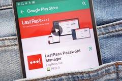 L'appli de directeur de mot de passe de LastPass sur le site Web de Google Play Store montré sur le smartphone caché dans des jea images stock