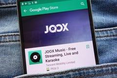 L'appli de JOOX sur le site Web de Google Play Store montré sur le smartphone caché dans des jeans empochent photos stock