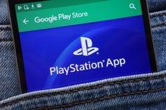 L'appli de PlayStation sur le site Web de Google Play Store montré sur le smartphone caché dans des jeans empochent images libres de droits