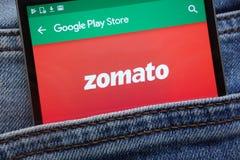 L'appli de Zomato sur le site Web de Google Play Store montré sur le smartphone caché dans des jeans empochent photographie stock libre de droits