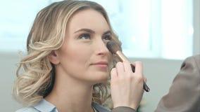 L'application rougissent maquillage avec la brosse aux pommettes de la jeune femme de sourire Photo libre de droits