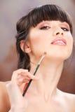 L'applicazione della donna compone con la spazzola Fotografia Stock