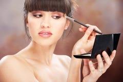 L'applicazione della donna compone con la spazzola Immagine Stock