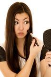 L'applicazione teenager americana asiatica sveglia arrossisce guardando in specchio Fotografie Stock Libere da Diritti