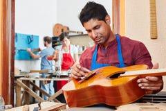 L'apprendista del creatore della chitarra ripara la chitarra Fotografia Stock