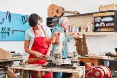 L'apprendista del liutaio lavora alla nuova chitarra Fotografia Stock Libera da Diritti
