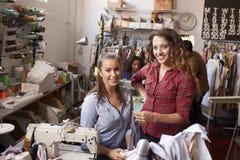 L'apprendista ed il responsabile allo studio di progettazione dei vestiti guardano alla macchina fotografica immagine stock libera da diritti