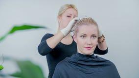 L'apprettatrice dei capelli ha legato i capelli sui capelli di colourd del cliente appena video d archivio