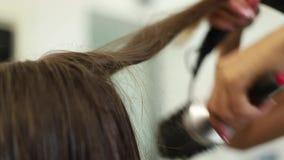 L'apprettatrice femminile professionale dei capelli ha usato un hairdryer La ragazza le che ottiene i capelli si è vestita nel sa archivi video