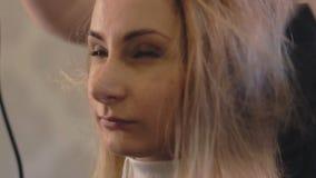 L'apprettatrice professionale dei capelli ha usato un hairdryer La giovane donna le che ottiene i capelli si è vestita nel salone video d archivio