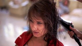 L'apprettatrice professionale dei capelli usa un hairdryer La giovane donna le che ottiene i capelli si è vestita nel salone di c video d archivio