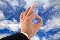 L'approvazione della mano firma dentro il cielo fotografie stock