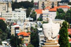 L'aquila di pietra bianca custodice il portone ai giardini di Bahai e trascura il paesaggio urbano di Haifa fotografie stock