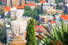 L'aquila di pietra bianca custodice il portone ai giardini di Bahai e trascura il paesaggio urbano di Haifa fotografia stock libera da diritti