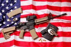 Fusil de l'AR, une bible et un pistolet sur le drapeau américain Images libres de droits