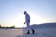 L'Arabe bel masculin sûr dans Kandur marche au milieu du blanc Photo stock