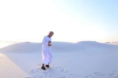 L'Arabe bel masculin sûr dans Kandur marche au milieu du blanc Image stock