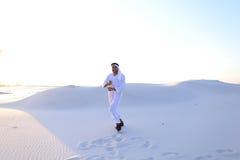 L'Arabe bel masculin sûr dans Kandur marche au milieu du blanc Photos stock