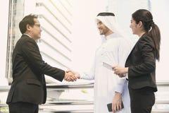 L'arabe d'homme d'affaires avec l'ingénieur concluant l'accord de poignée de main Image stock