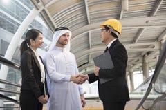 L'arabe d'homme d'affaires avec l'ingénieur concluant l'accord de poignée de main Images stock