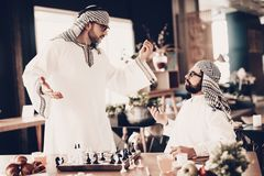 L'Arabe ne comprend pas comment perdre dans les échecs images stock