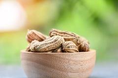 L'arachide à l'arrière-plan en bois de vert de cuvette et de nature a bouilli des arachides images stock