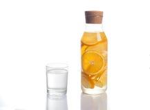 L'arancia ed il limone hanno infuso l'acqua in un decantatore di vetro su fondo bianco Fotografia Stock
