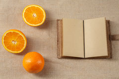 L'arancia ed il taccuino aperto che si trovano su una tela di sacco sorgono Immagini Stock Libere da Diritti
