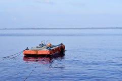 L'arancia ha dipinto la chiatta del metallo ancorata lungo la baia dell'oceano immagine stock libera da diritti