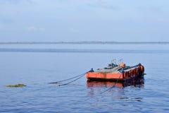 L'arancia ha dipinto la chiatta del metallo ancorata lungo la baia dell'oceano fotografia stock libera da diritti