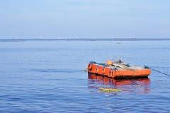L'arancia ha dipinto la chiatta del metallo ancorata lungo la baia dell'oceano fotografia stock
