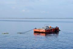 L'arancia ha dipinto la chiatta del metallo ancorata lungo la baia dell'oceano fotografie stock libere da diritti