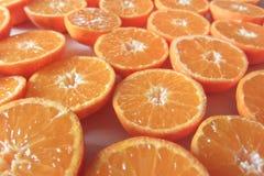 L'arancia ha tagliato i mandarini su una tavola come fondo Fotografia Stock