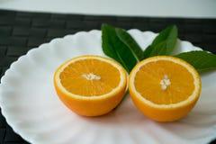 L'arancia organica della fetta sul piatto bianco - Immagini Stock