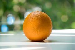 L'arancia organica su fondo vago verde Immagine Stock Libera da Diritti
