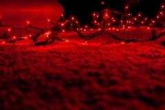 L'arbre de Noël abstrait s'allume dans le bokeh foncé et rouge, brouillent defocused, tache floue defocused photo stock