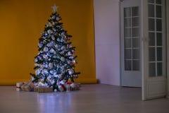 L'arbre de Noël avec des présents, guirlande allume la nouvelle année Image libre de droits