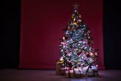 L'arbre de Noël avec des présents, guirlande allume la nouvelle année Images stock
