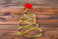 L'arbre de Noël avec le ruban et le rouge se tient le premier rôle sur le fond en bois Image stock