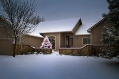 L'arbre de Noël couvert par neige rougeoie comme par magie dans cette scène d'hiver Photos libres de droits