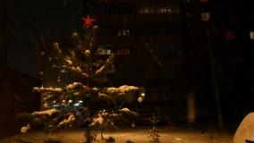 L'arbre de Noël décoré se tient sur la rue la nuit, dans des chutes de neige, une étoile rouge sur le dessus de la tête clips vidéos