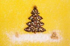 L'arbre de Noël des grains de café et des cadeaux de Noël des gaufres a décoré des puces de noix de coco sur un fond jaune photo stock