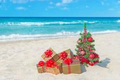 L'arbre de Noël et le cadeau d'or avec le grand arc rouge sur la mer échouent Photographie stock