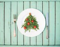 L'arbre de Noël fait en arugula et les tomates-cerises sur le blanc plat Photos stock