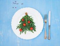 L'arbre de Noël fait en arugula et les tomates-cerises sur le blanc plat Photo libre de droits