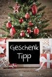 L'arbre de Noël nostalgique avec Geschenk Tipp signifie l'astuce de cadeau Photo stock