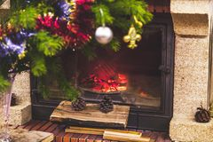 L'arbre de Noël se tient devant la cheminée avec le bois de chauffage brûlant image stock