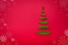 L'arbre de Noël de symbole d'un sapin s'embranche sur le fond rouge cop Photos stock